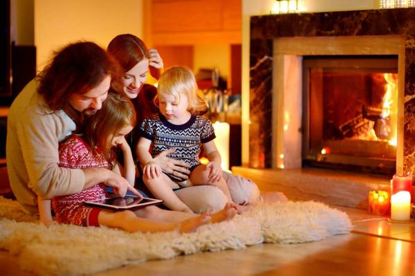 Family by a warm fire enjoying their insulated home